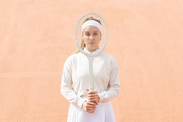 Jeune femme couvrir le visage avec une raquette de tennis