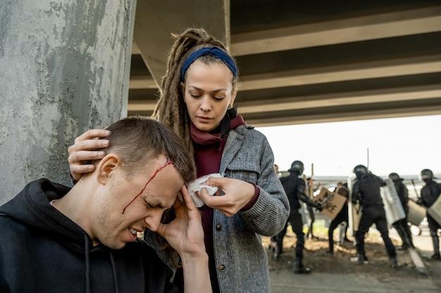 Jeune femme avec des craintes mettant un bandage sur la tête de l'homme a souffert dans la lutte des rebelles et de la police anti-émeute, femme aidant à arrêter le sang à la victime