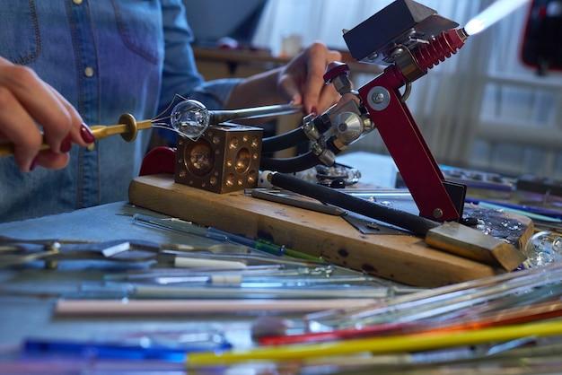 Jeune femme créative assise par table en atelier en face de brûleur de travail et de fixation de petite pièce en verre à l'aide de handtool