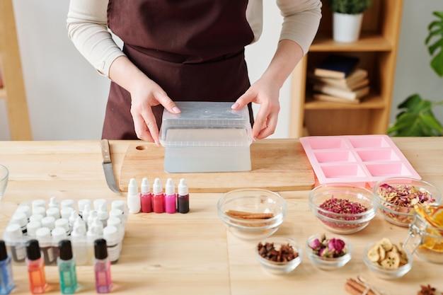 Jeune femme créative en prenant une barre de masse de savon dur hors de récipient en plastique et en la mettant sur une planche de bois