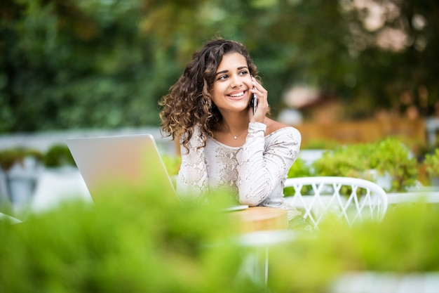 Jeune femme créative travaille sur ordinateur portable tout en prenant son petit déjeuner sur la terrasse