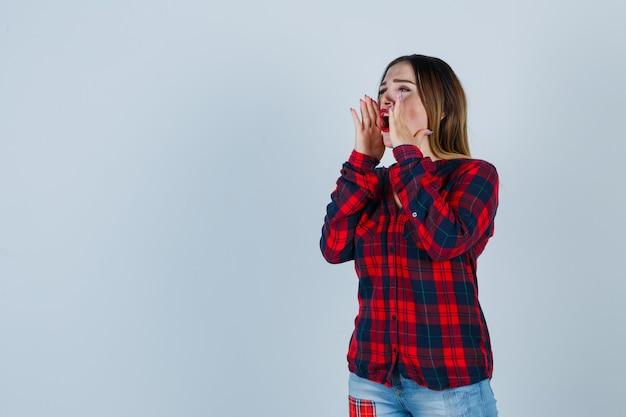 Jeune femme criant ou annonçant quelque chose en chemise à carreaux et semblant induite. vue de face.