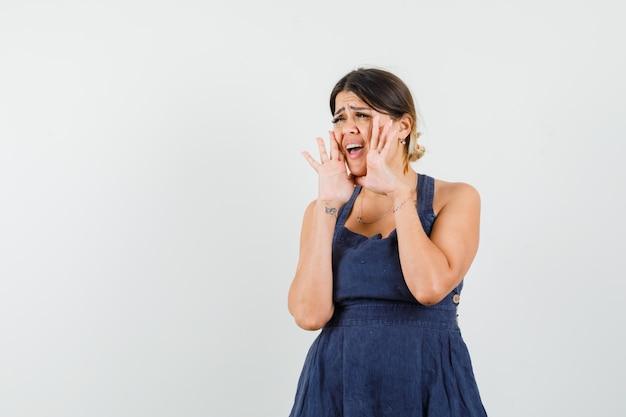 Jeune femme criant ou annonçant quelque chose en robe
