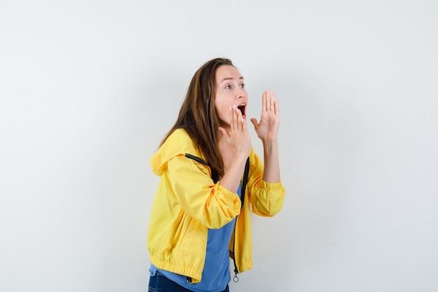 Jeune femme criant ou annonçant quelque chose en t-shirt, veste et semblant excitée, vue de face.