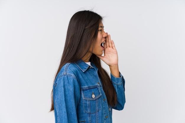 Jeune femme criant et tenant la paume près de la bouche ouverte.