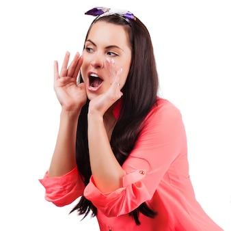 Jeune femme crier et crier en utilisant ses mains comme tube,