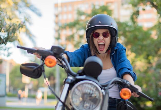 Jeune femme crier sur une moto