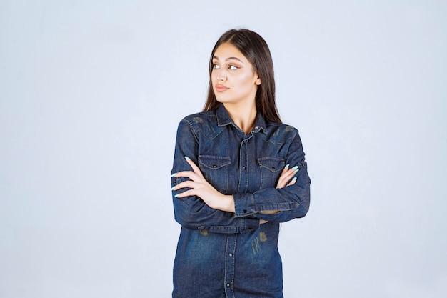 Jeune femme croisant les bras et donnant des poses professionnelles