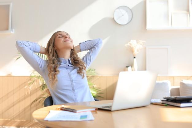 Jeune femme a croisé les mains derrière la tête, profitant d'une pause à la maison. femme d'affaires paisible et insouciante se reposant à table avec un ordinateur, regardant de côté, rêvant de l'avenir