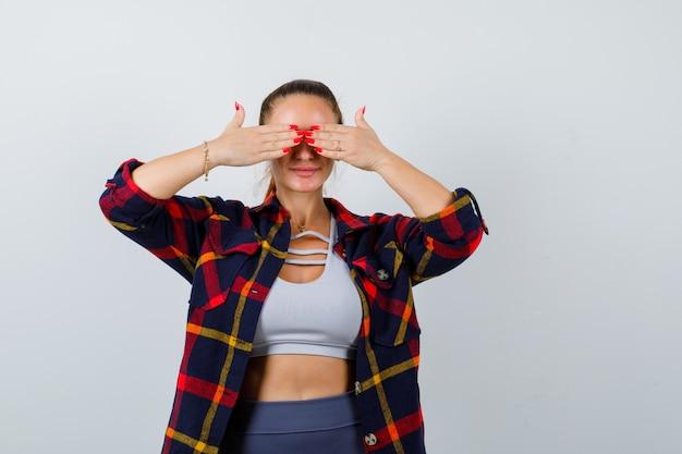 Jeune femme en crop top, chemise à carreaux, pantalon avec les mains sur les yeux et l'air mignon, vue de face.