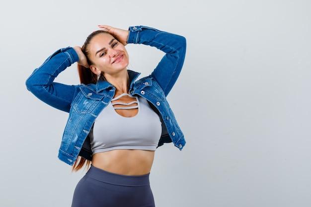 Jeune femme en crop top, veste, pantalon avec les mains sur la tête et l'air joyeux, vue de face.