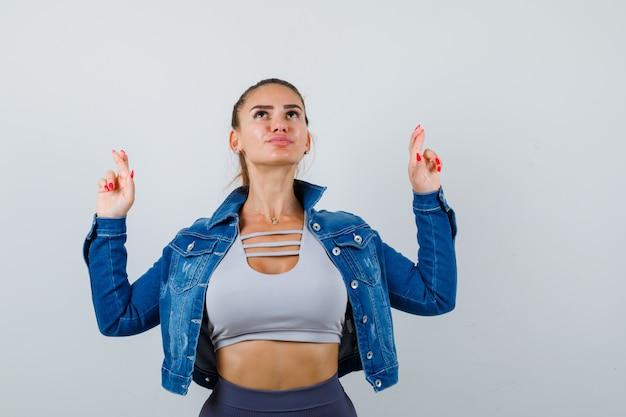 Jeune femme en crop top, veste, pantalon montrant les doigts croisés et l'air plein d'espoir, vue de face.