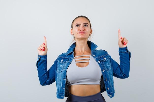 Jeune femme en crop top, veste, pantalon pointant vers le haut et hésitant, vue de face.