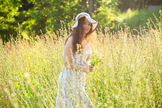 Jeune femme cueillant des fleurs dans le pré en soirée d'été