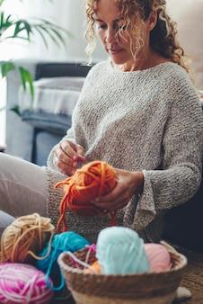 Jeune femme cueillant la laine du panier alors qu'elle était assise sur le sol à la maison. belle femme se préparant à tricoter de la laine tout en se relaxant à la maison. femme de race blanche avec des boules de laine dans le panier.