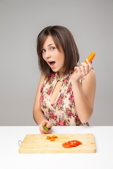Jeune femme cuisinant dans la cuisine. alimentation saine - salade de légumes. diète. concept de régime. mode de vie sain. préparer la nourriture