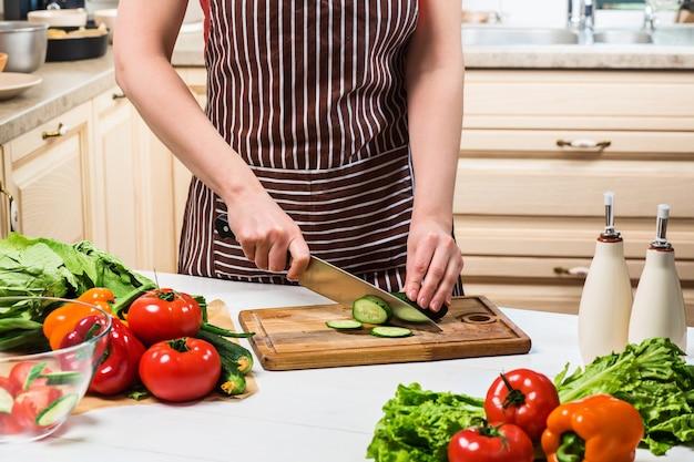 Jeune femme cuisinant dans la cuisine à la maison. nourriture saine. diète. concept de régime. mode de vie sain. cuisiner à la maison. préparer la nourriture. une femme coupe un concombre et des légumes avec un couteau.