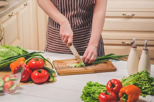 Jeune femme cuisinant dans la cuisine à la maison. nourriture saine. diète. concept de régime. mode de vie sain. cuisiner à la maison. préparer la nourriture. une femme coupe un oignon vert et des légumes avec un couteau.