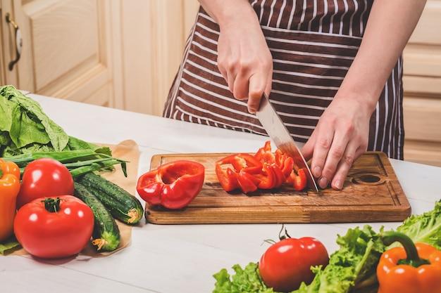Jeune femme cuisinant dans la cuisine à la maison. nourriture saine. diète. concept de régime. mode de vie sain. cuisiner à la maison. préparer la nourriture. une femme coupe un poivron et des légumes avec un couteau.