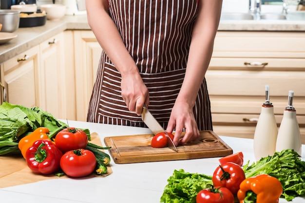Jeune femme cuisinant dans la cuisine à la maison. nourriture saine. diète. concept de régime. mode de vie sain. cuisiner à la maison. préparer la nourriture. une femme coupe une tomate et des légumes avec un couteau.