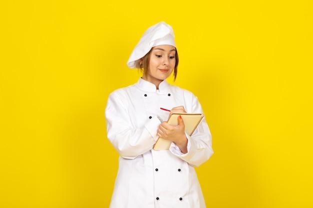 Jeune femme cuisine en costume de cuisinier blanc et bonnet blanc en écrivant des notes
