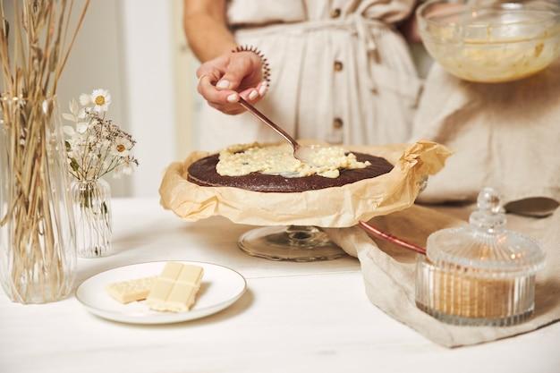 Jeune femme cuisinier faisant un délicieux gâteau au chocolat avec de la crème sur une table blanche