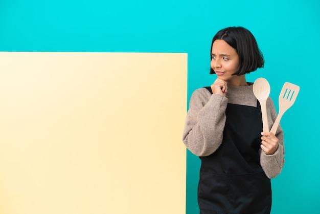 Jeune femme de cuisinier de race mixte avec une grande pancarte isolée sur fond bleu ayant des doutes