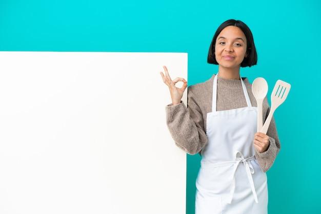 Jeune femme de cuisinier de race mixte avec une grande pancarte isolée sur fond bleu dans une pose zen