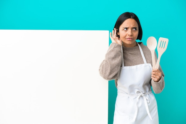 Jeune femme de cuisinier de race mixte avec une grande pancarte isolée sur fond bleu écoutant quelque chose en mettant la main sur l'oreille
