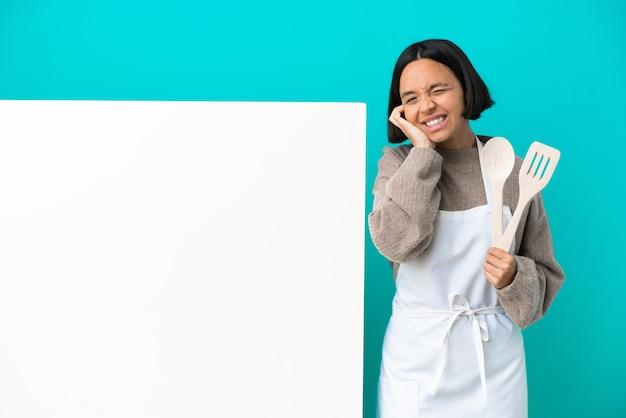 Jeune femme de cuisinier de race mixte avec une grande pancarte isolée sur fond bleu frustré et couvrant les oreilles
