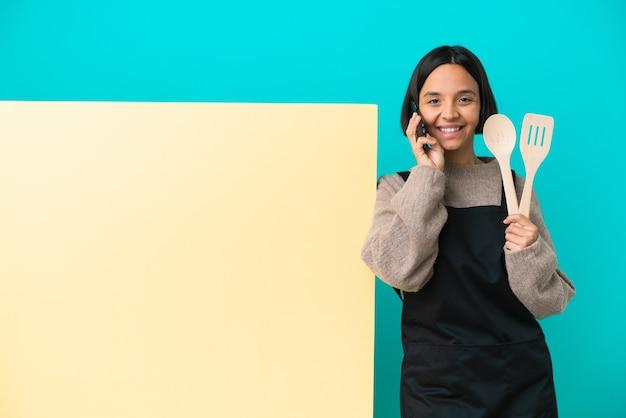 Jeune femme de cuisinier de race mixte avec une grande pancarte isolée sur fond bleu gardant une conversation avec le téléphone portable avec quelqu'un