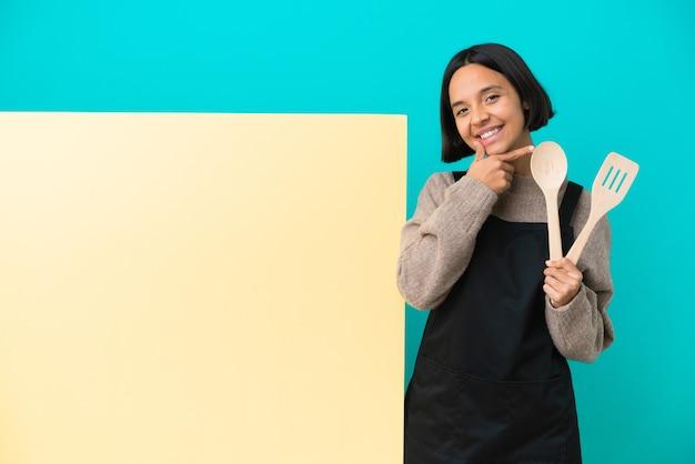 Jeune femme de cuisinier de race mixte avec une grande pancarte isolée sur fond bleu heureux et souriant