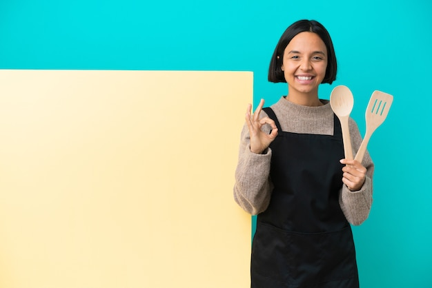 Jeune femme de cuisinier de race mixte avec une grande pancarte isolée sur fond bleu montrant un signe ok avec les deux mains