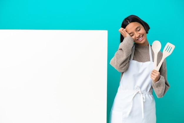 Jeune femme de cuisinier de race mixte avec une grande pancarte isolée sur fond bleu en riant