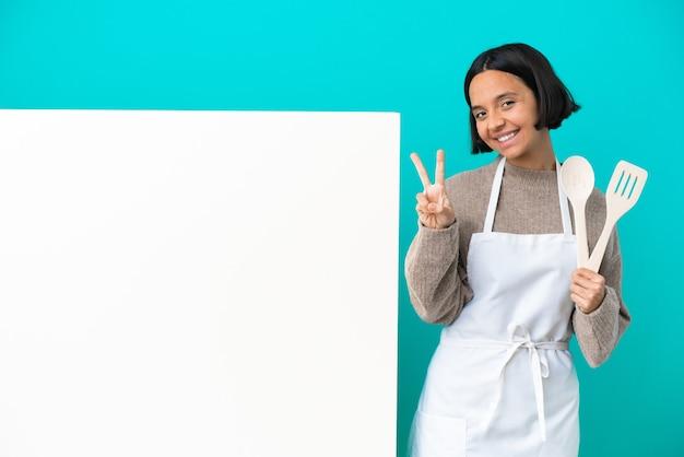 Jeune femme de cuisinier de race mixte avec une grande pancarte isolée sur fond bleu souriant et montrant le signe de la victoire
