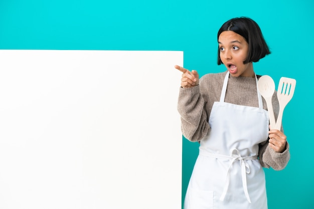 Jeune femme de cuisinier de race mixte avec une grande pancarte isolée sur fond bleu surpris et pointant vers le haut