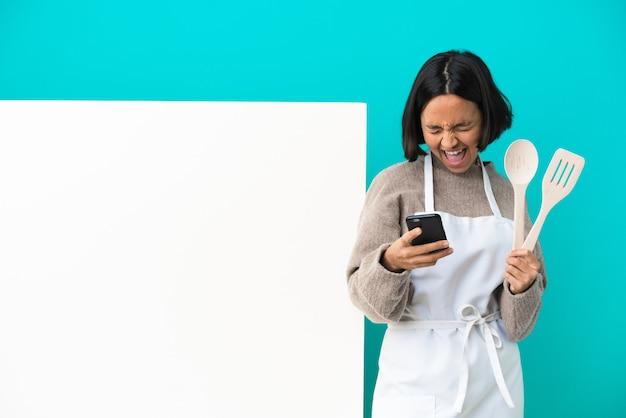 Jeune femme de cuisinier de race mixte avec une grande pancarte isolée sur fond bleu avec téléphone en position de victoire
