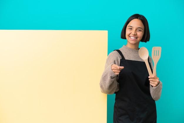 Jeune femme de cuisinier de race mixte avec une grande pancarte isolée pointant vers l'avant avec une expression heureuse