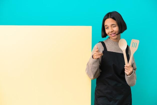 Jeune femme de cuisinier de race mixte avec une grande pancarte isolée pointant vers l'avant et souriante