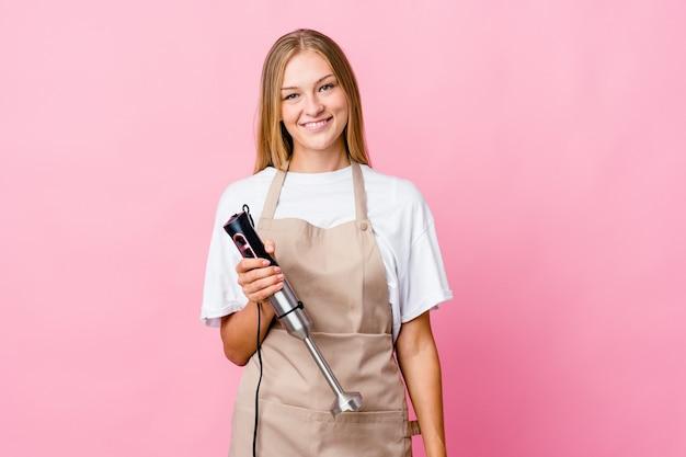 Jeune femme de cuisinier russe tenant un batteur électrique isolé heureux, souriant et joyeux