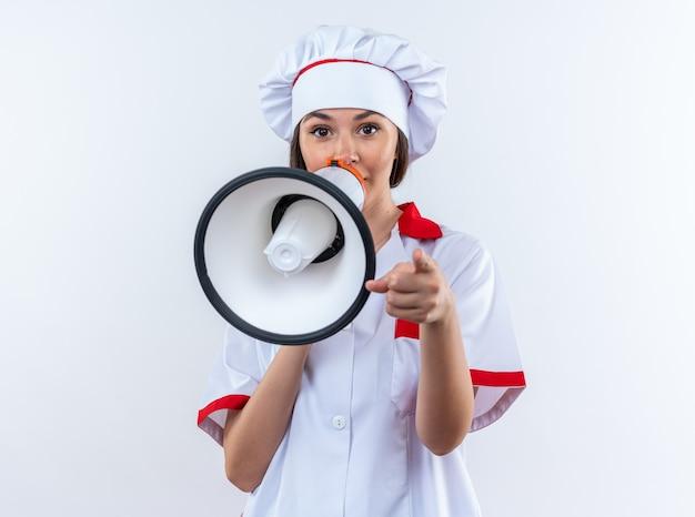 Jeune femme cuisinier en uniforme de chef parle sur haut-parleur isolé sur fond blanc