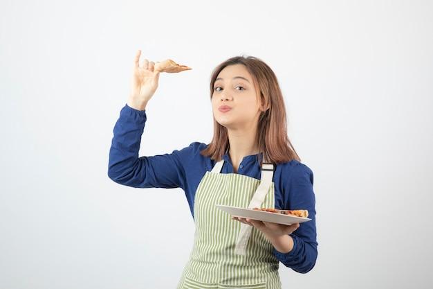 Jeune femme cuisinière tenant une assiette de délicieuses pizzas.
