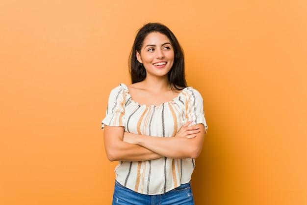 Jeune femme curvy souriante confiante avec les bras croisés