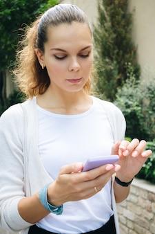 Jeune femme, dans, affaires, vêtements, marcher bas, rue, et, utilisation, a, téléphone portable, à, écran tactile