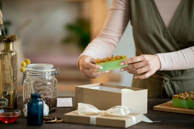 Jeune femme dans un bar d'emballage de vêtements décontractés de savon naturel frais fait à la main dans une boîte-cadeau en carton tout en préparant des cadeaux pour ses amis