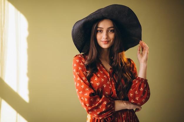 Jeune femme dans une belle robe et un chapeau