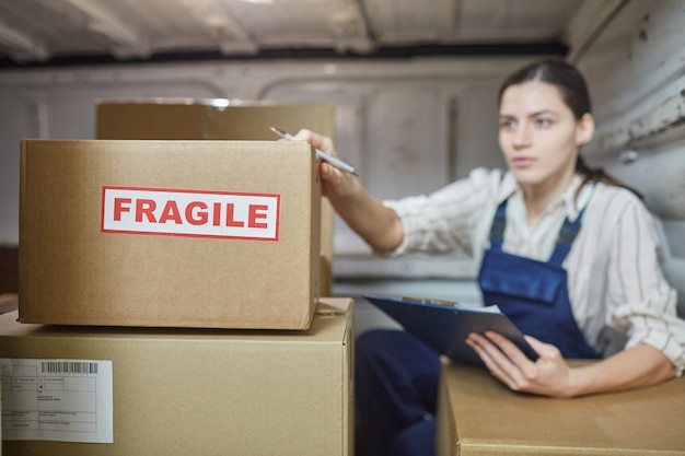 Jeune femme dans les boîtes d'enregistrement unifrom avant la livraison