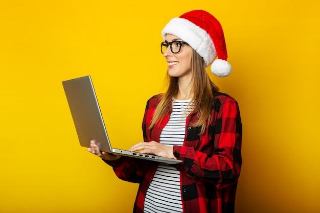 Jeune femme dans un bonnet de noel et une chemise rouge dans une cage est titulaire d'un ordinateur portable