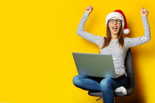 Jeune femme dans un bonnet de noel avec un visage heureux est assis sur une chaise et tient un ordinateur portable