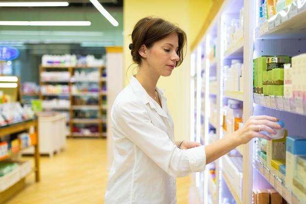 Jeune femme dans une boutique de cosmétiques choisit une crème de soin de la peau